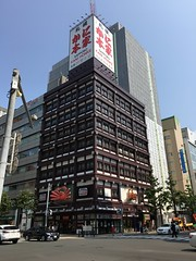 Motionless Crab Building 1 (sjrankin) Tags: 10july2019 hokkaido japan sapporo downtown buildings restaurant crab road intersection cars people