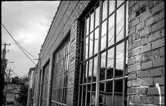 large windows, reflections, near dusk, industrial architecture, West Asheville, NC, FED 4, Derev Pan 200, HC-110 developer, 7.8.19 (steve aimone) Tags: windows windowpanes reflections industrialarchitecture urbanlandscape neardusk westasheville northcarolina fed4 derevpan200 hc110developer rangefinder soviet 35mm 35mmfilm film monochrome monochromatic blackandwhite
