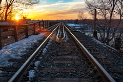 Sunset Tracks (B.E.K. Photography) Tags: saskatoon saskatchewan canada bridge train tracks rails cloud sky sunset cpr trees winter snow evening river water blue white yellow orange red flare starburst bek briankrouskie outdoor landscape nikond850