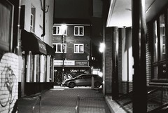 Thrawl Street (goodfella2459) Tags: nikonf4 afnikkor50mmf14dlens kodaktrix400 35mm blackandwhite film analog night streets city london whitechapel thrawlstreet bricklane car buildings eastend maryannnichols history crimehistory jacktheripper bwfp