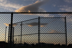 Multiple fences = overlapping linear patterns (Jon Dev) Tags: silhouettes contrast clouds sunset poles lightposts chainlinkfence