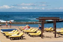 Paseo Orinoco, Playa de las Américas, Arona, Santa Cruz de Tenerife, Canary Islands (wildhareuk) Tags: beach canaryislands canon canoneos500d people sand sea seascape spain sunbed tamron18270mm tenerife tenerife2019 water pergola tamron img9503dxo