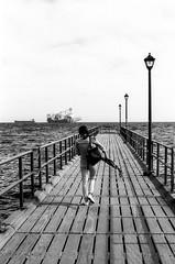 Off she goes... (mozo273) Tags: wood old sea sky blackandwhite bw woman film girl monochrome analog canon person lights pier seaside mediterranean waves ship walk cyprus eos30 bnw limassol xtol fomapan100 fomapan pushprocessing fomafilm