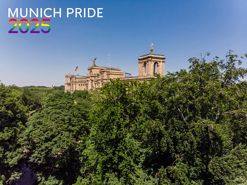 """Maximilianeum behind green trees and blue sky with the picture title """"Munich Pride 2025"""" in rainbow-colors, for the Christopher-Street-Day Festival"""