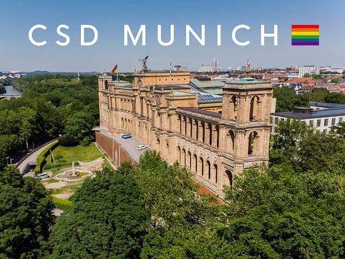 """""""CSD Munich"""" Bildtitel mit einer Regenbogenflagge und der Sehenswürdigkeit Maximilianeum in München"""