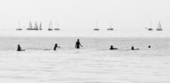 Boats and Bathers (brucetopher) Tags: beach sea man woman water wet bay waves ripples boat boating sail sailing sailor swim swimming surf boogieboard sails silhouette people figures shallow wind kids vacation holiday men women highkey contrast black white blackandwhite bw blackwhite monochrome mono bnw