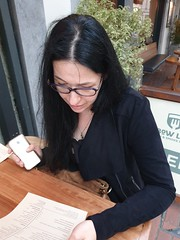 Nina Studying the menu...in Cork City... July 2019 (sean and nina) Tags: cork city county ireland irish eire tourist tourism holiday visit pubs bars restaurant blue eu europe european people places nina woman female girl lady girlfriend fiancee wife married brunette long dark hair glasses black dress clothes cardigan outdoor public candid unposed face menu wooden table gorgeous stunning beauty beautiful charm chamring building street persons outside centre