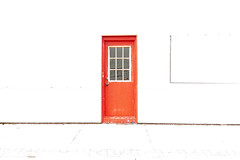 Red door on a white wall (bill.d) Tags: ioniacounty lakeodessa michigan us unitedstates door outdoor sunny red explored