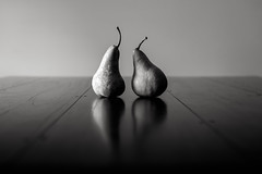 and then there was one... (Tony Macrellis) Tags: endoftheromance endings twopear pear pears blackandwhite bw mykittchentable availablelight reflection movingon contemplation stilllife still life tonymacrellis tony macrellis asymmetry twopears
