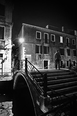 Italian street photography Venice (www.streetphotography-berlin.com) Tags: venice italy night street streetphotography streetlife bridge canal man alone light shadow lamp fineart blackandwhite blackwhite monochrome high contrast