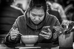 Multitasking (Grant Grieve. Off the grid.) Tags: phone lady woman girl bowl noodles multitask chopsticks farmers market candid street portrait city contrast photography photo strangers women monochrome monotone mono noiretblanc bw black white urban life people provoke faces decisive moment canon ef85mmf14lisusm prime canoneos5dmarkiv 5dmkiv streetphotography