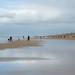 Praia cheia de pessoas encasacadas