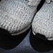 Close up of knitted sneakers on black surface