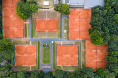 Aerial shot of several orange tennis courts, surrounded by forrest, in Cologne - Müngersdorf