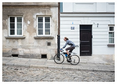 Racing Uphill (Dave Button) Tags: warsaw poland oldtown bike bicycle color colour fuji fujifilm street streetphotography urban xe2 xe2s blur blurred