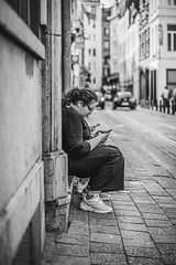 Killing time on the phone (Sjaco Manuputty) Tags: street streetphotography bnw blackandwhite sidewalk road city antwerp antwerpen people phone smartphone