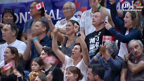 Sensei Rick Hatashita sitting between two of his relatives, all watching the 2019 Grand Prix judo action in Montreal Quebec Canada