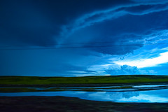 Under the Supercell (darletts56) Tags: sky skyline cloud clouds blue white supercell storm wind still wire wires line lines field fields green water dugout saskatchewan canada prairie grey reflection formation formations traveling movement black grass