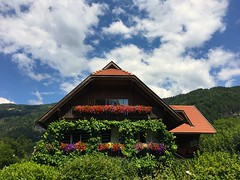 Beautiful Carinthian-style house (echumachenco) Tags: wood blue summer sky cloud house building architecture austria österreich july kärnten carinthia mountainside iphone ossiachersee steindorf roof flower balcony greenery geranium