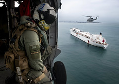 Naval Aircrewman flies in an MH-60S Sea Hawk over the hospital ship USNS Comfort.