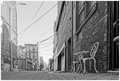 2019/194: Alley, Table for Two (Rex Block) Tags: nikon d750 dslr 1835mm wide zoom washington dc alley table chairs wires bricks utility monochrome bw project365 365the2019edition 3652019 day194365 13jul19 ekkidee 2019194alleytablefortwo