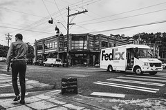 Street Scene: Intersection (oterrason) Tags: street streetscene road truck fedex man crosswalk blackandwhite monochrome monochromatic clouds electricwires sky delivery starbucks coffeeshop magnolia seattle people vehicles transitpowerlines signage sidewalk advertisingboard building fujinonxf16mmf14rwr fuji fujifilmxt2