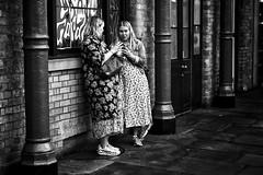 Frock Friends (garryknight) Tags: sony a6000 on1photoraw2018 london themonoseries monochrome blackandwhite snapseed coventgarden woman friend frock street candid