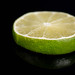 Slice of Lime fruit on the black reflective background