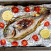Baked with vegetables Dorado fish on foil in a baking sheet
