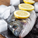 Raw Dorado fish with ice and lemon slices close-up thumbnail