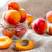 Glass jar with apricots on burlap background