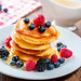 Delicious homemade golden pancakes with fresh raspberries, blueberries and mulberry