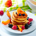 Stack of pancakes with fruit blueberries, raspberries, mulberry, apricot pieces and honey