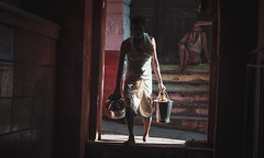 Scorched Delivery (Camille Marotte) Tags: india varanasi 2014 street door travel sun man streets contrast canon walking darkness indian poor streetphotography sigma tunnel delivery cinematography cinematic traditionnal
