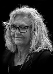 Portrait (D80_539210) (Itzick) Tags: denmark copenhagen candid bw blackbackground bwportrait woman glasess streetphotography smiling face facialexpression necklace portrait d800 itzick