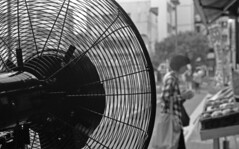 Fan at a vegetable shop (odeleapple) Tags: leica llla canon 50mm yellowfilter kodaktmax100 film monochrome analog bw fan vegetable shop woman