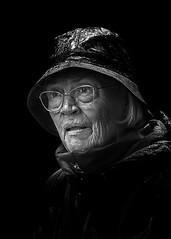 Portrait (D80_538962) (Itzick) Tags: denmark copenhagen candid woman bw blackbackground hat glasess streetphotography face facialexpression portrait d800 itzick