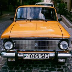 Yellow Russian Sedan (Packing-Light) Tags: 35mm azerbaijan baku caucasus eurasia nikonf6 analog emulsion film fujicolor fuji superia400 city street