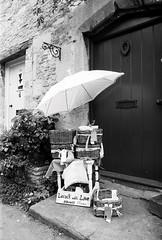 In Lacock village (a.pierre4840) Tags: olympus om2n zuiko 24mm f28 35mmfilm ilford ilfordfp4 fp4 bw blackandwhite noiretblanc doors umbrella wiltshire england
