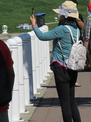 Recording the sights (jamica1) Tags: kelowna downtown waterfront okanagan bc british colulmbia canada photography photographer hat backpack woman