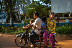 Family on a Country Road (shapeshift) Tags: asia cambodia countryroad davidpham davidphamsf documentary family mother motorcycle people road scooter shapeshift shapeshiftnet siempreap southeastasia stores street streetphotography transport transportation travel russeiluk siemreapprovince