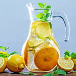 Glass of lemonade with ice cubes and mint leaves on wooden background thumbnail