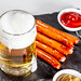 Beer mug with sauces and sausages on a black stone tray