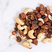 Energy mix with raisins hazelnuts cashew and brazilian nuts on the marble table