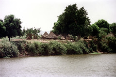 79-302 (ndpa / s. lundeen, archivist) Tags: nick dewolf color photograph photographbynickdewolf 1976 1970s film 35mm 79 reel79 africa northernafrica northeastafrica african ethiopia ethiopian southernethiopia water river watersedge riversedge riverbank village buildings huts houses homes thatchroof thatchedroof sky
