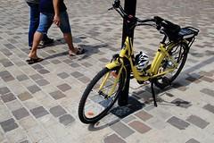 A pied, à vélo... (Tonton Gilles) Tags: pavés carrés rectangles vélocipède bicyclette vélo jaune graphisme passants jambes pieds personnages scène de rue réverbère lampadaire lignes brun bordeau rouge