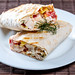 Cut Shawarma with chicken fillet and vegetables on a white plate