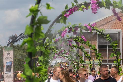 Festivalbesucher kühlen sich unter Blumentoren mit Spritzwasser ab, neben ihnen ein Schild wirbt das offizielle Festival-App von Tomorrowland