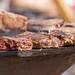 Saftig gebratene, noch leicht blutige Koteletts von OFYR auf Grillplatte am Tomorrowland Festival 2019