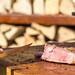 Nahaufnahme von noch leicht blutigem, frisch geschnittenem Stück Grillfleisch auf Holztisch